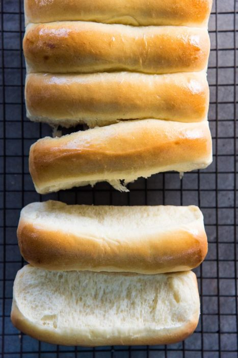 New England Hot Dog Buns on a wire rack, with the buns separated from each other to show the soft sides.