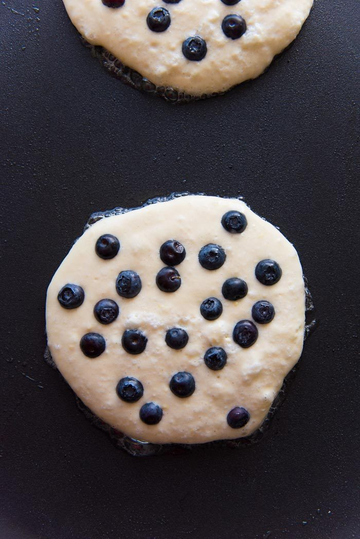 Blueberry pancakes being cooked on a griddle with blueberries placed on top.