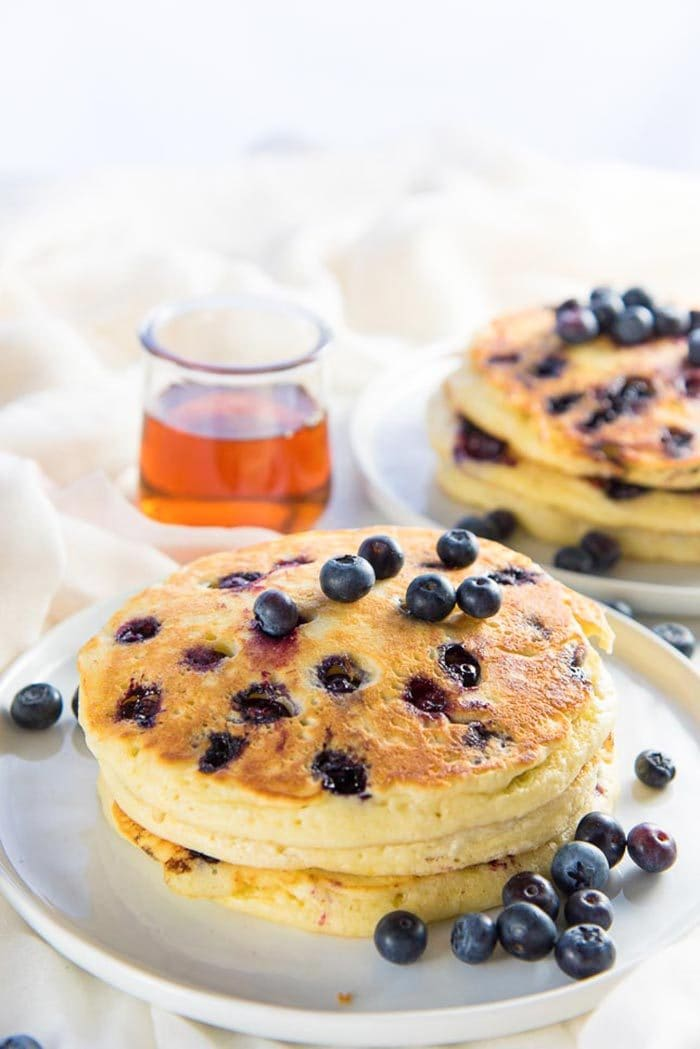 A stack of fluffy and delicious blueberry pancakes served on a white plate, with maple syrup in the background.