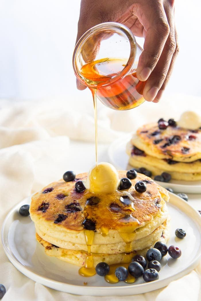 Stack of fluffy blueberry pancakes on a white plate, topped with butter, and fresh blueberries and maple syrup being poured over.