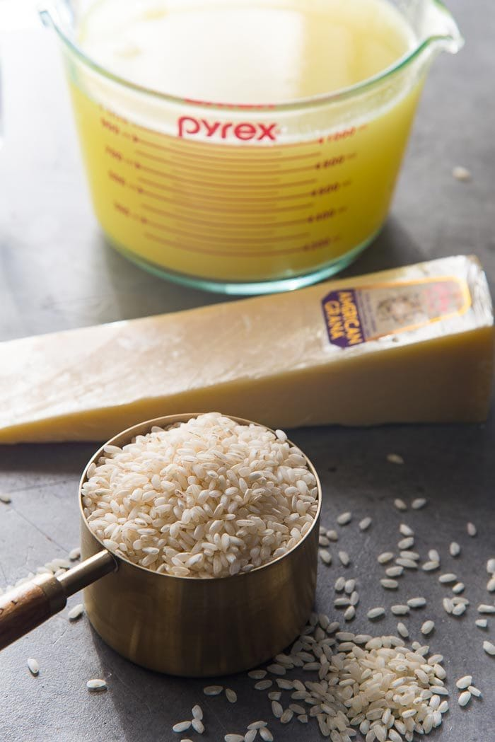 3 main ingredients needed to make risotto on a grey table - arborio rice, parmesan and stock.