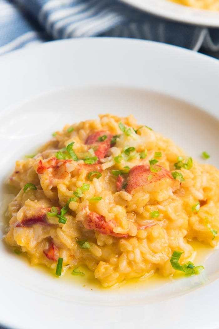 Butter poached lobster risotto served in a white serving dish, with chopped spring onions on top.