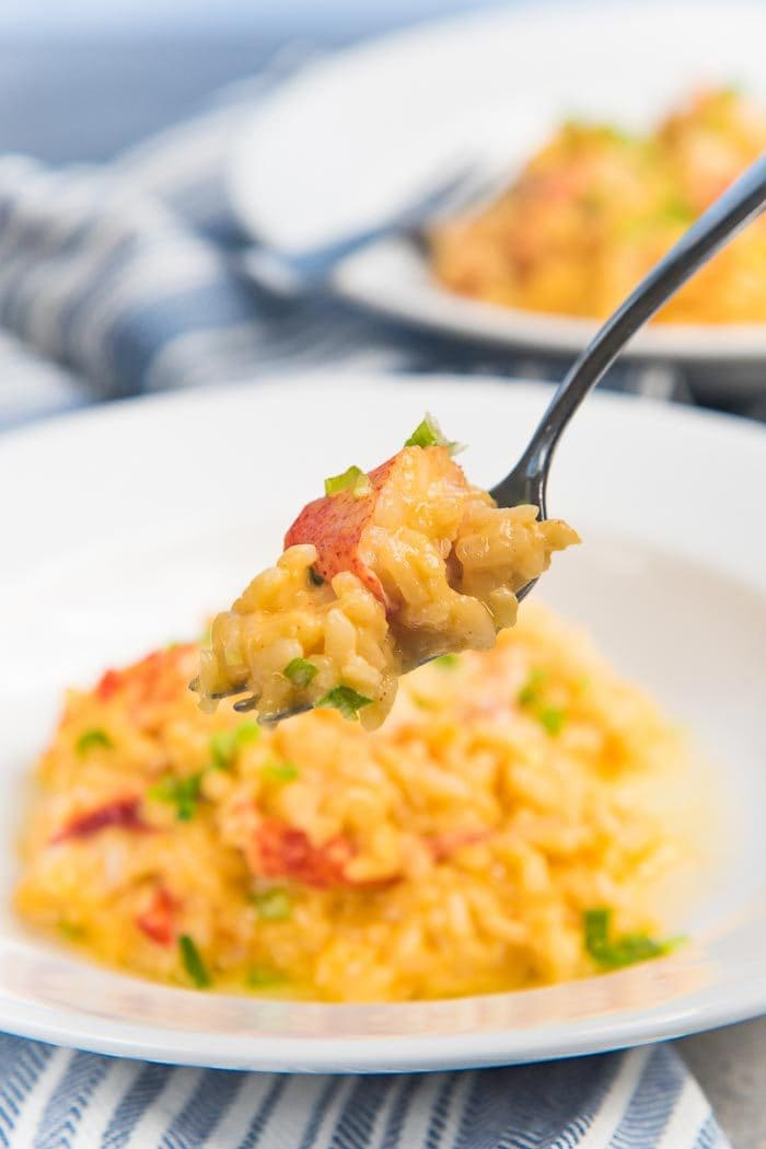 A fork with lobster risotto in the foreground, with the plate of lobster risotto in the background.