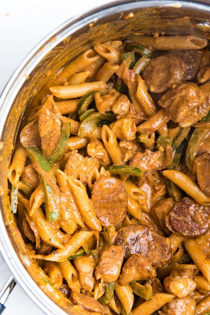 Penne pasta mixed into the cajun chicken pasta in a pot.