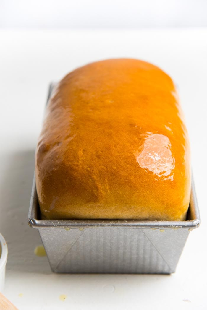 A perfectly baked, golden homemade bread loaf while still in the pan.