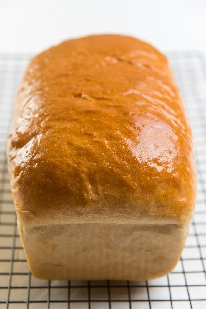 Baked homemade bread loaf cooling down on a wire rack.