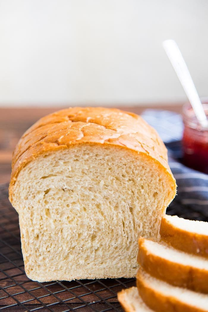 A close up of the baked homemade white bread, showing the crumb, next to a stack of sliced bread.
