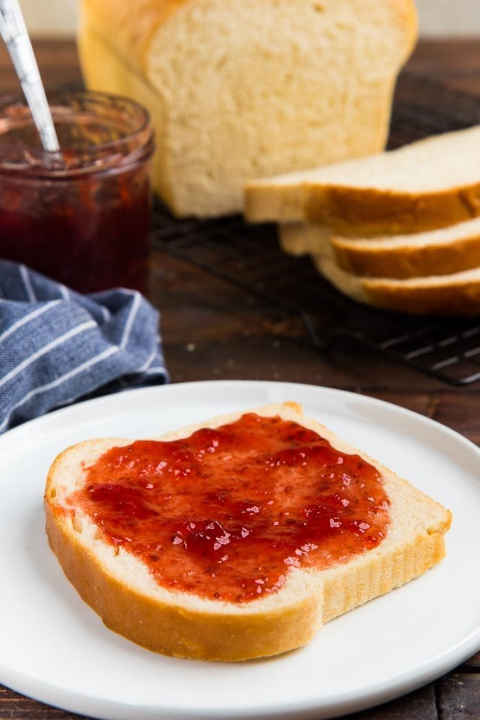 A slice of homemade bread on a white plate with jam spread on top, with the rest of the bread loaf in the background.