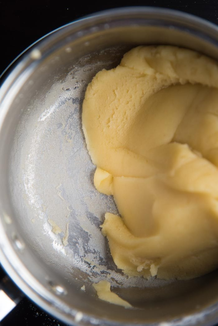 Step by step classic eclair recipe - Stir and mix the dough until the dough comes together to form a ball, and a film of dough forms at the bottom of the pot