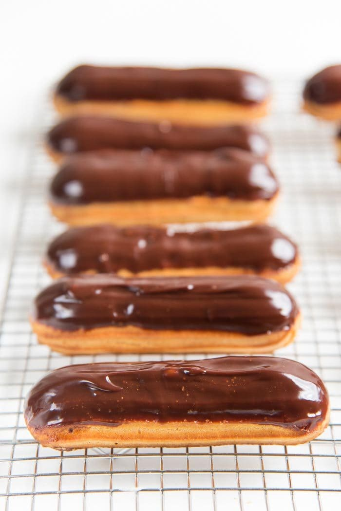 A row of chocolate eclairs on a wire rack
