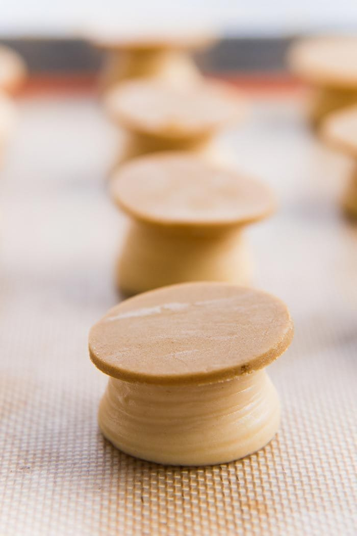 Craqueline discs placed on top of piped choux pastry dough