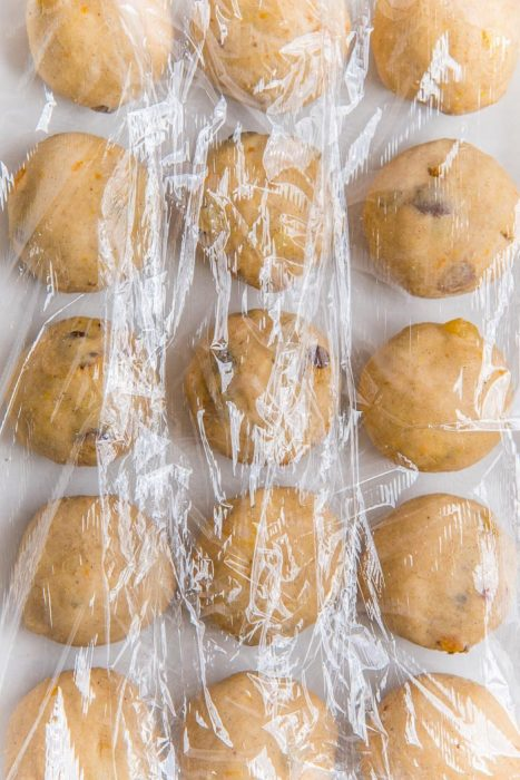 Individual hot cross buns, shaped into smooth balls and placed on top of a parchment lined baking tray, and covered with plastic wrap, for proofing.