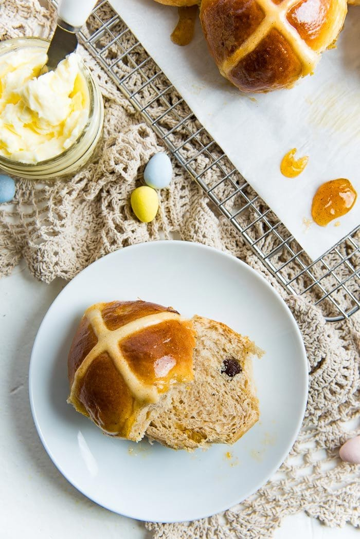 A soft hot cross bun cut in half on a small white plate, with a butter bowl next to it.