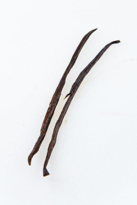 A close up of the vanilla bean split in half