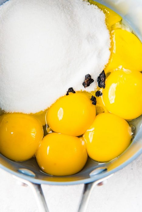 Ingredients to make Vanilla Ice cream - egg yolks, sugar, vanilla in a saucepan