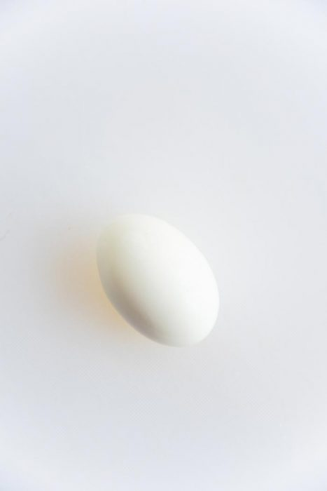 A half boiled egg on a white cutting board