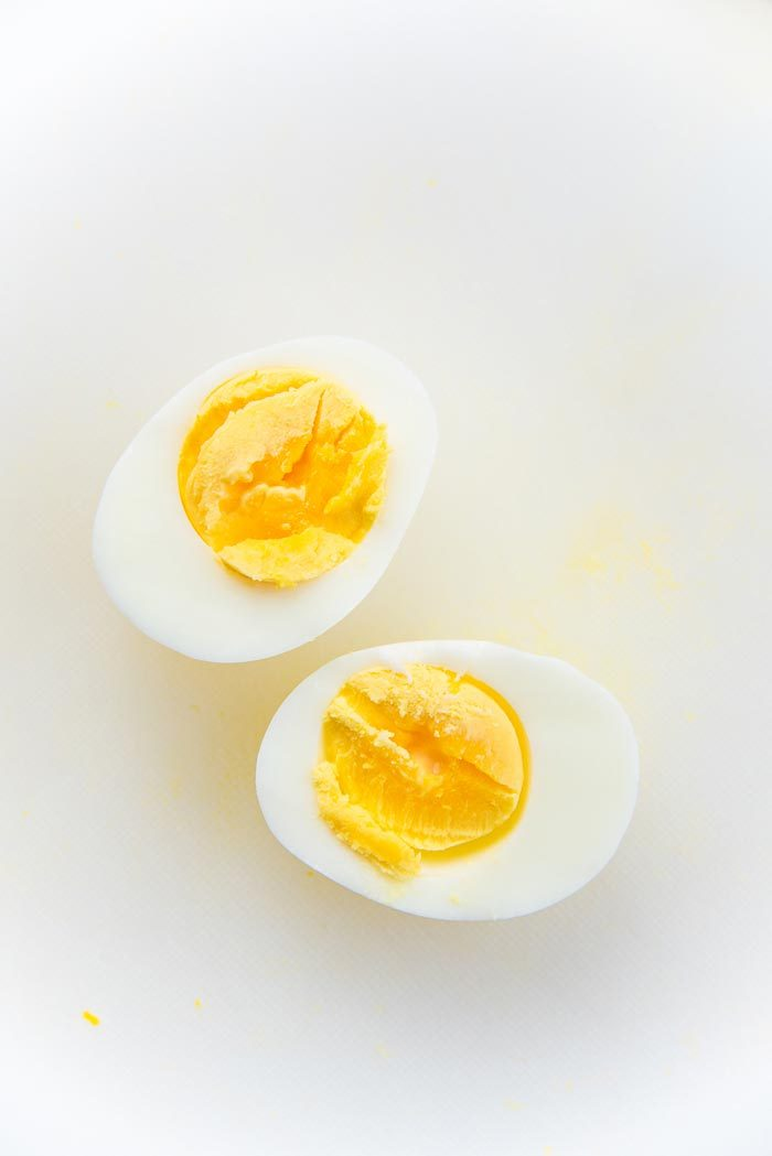 Half boiled egg cut in half to show the yellow cooked yolk.