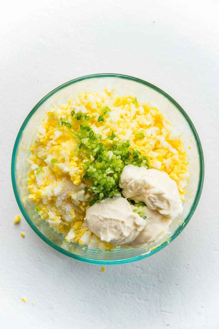 Chopped half boiled egg in a glass bowl, with salt, white pepper, sugar, spring onions and mayonnaise.