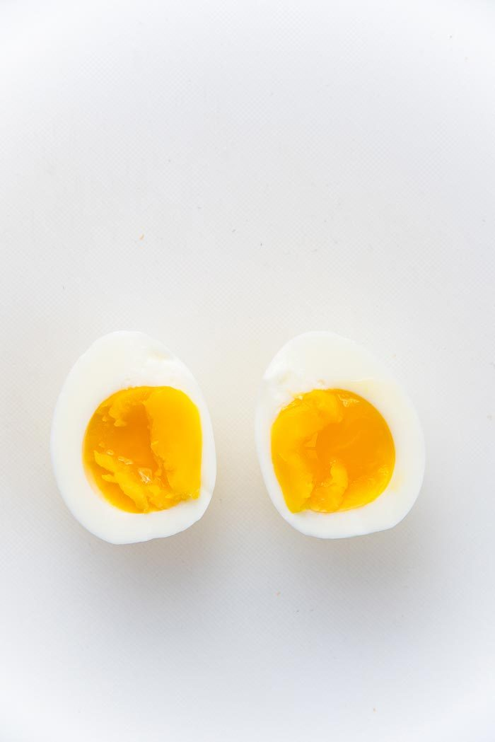 A soft boiled egg with a jammy yolk, cut in half on a cutting board