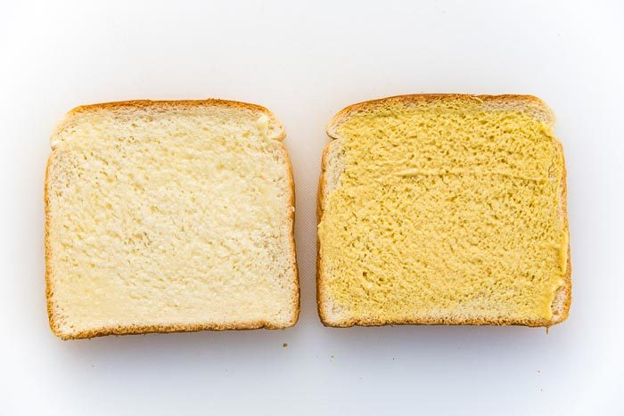 Two slices of bread, with butter and mustard spread on it.