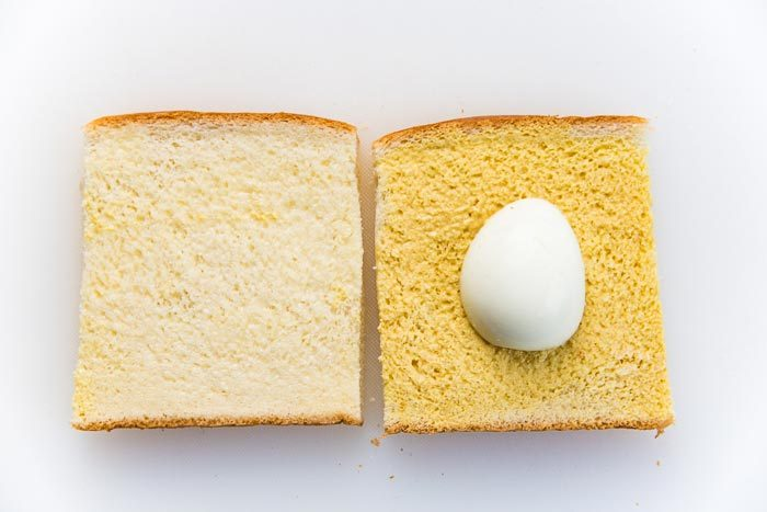 A half boiled egg placed on a sandwich bread slice