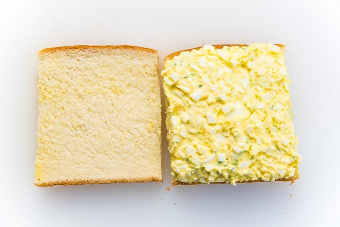 The egg salad filling, spread evenly on the slice of bread