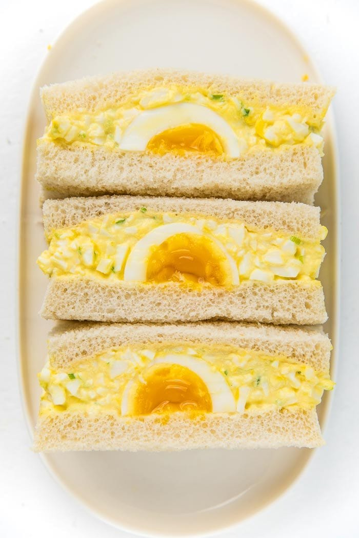 A close up of the three Japanese egg salad sandwiches on a white plate, with the soft boiled egg facing up
