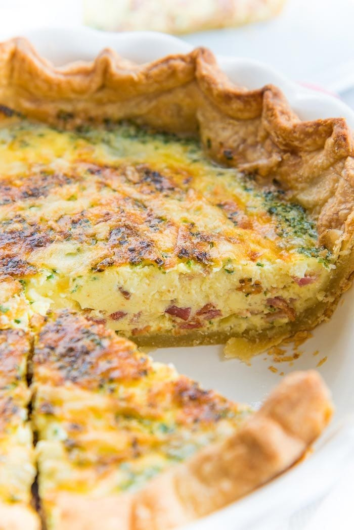 Quiche Lorraine in a quiche dish with one slice taken out
