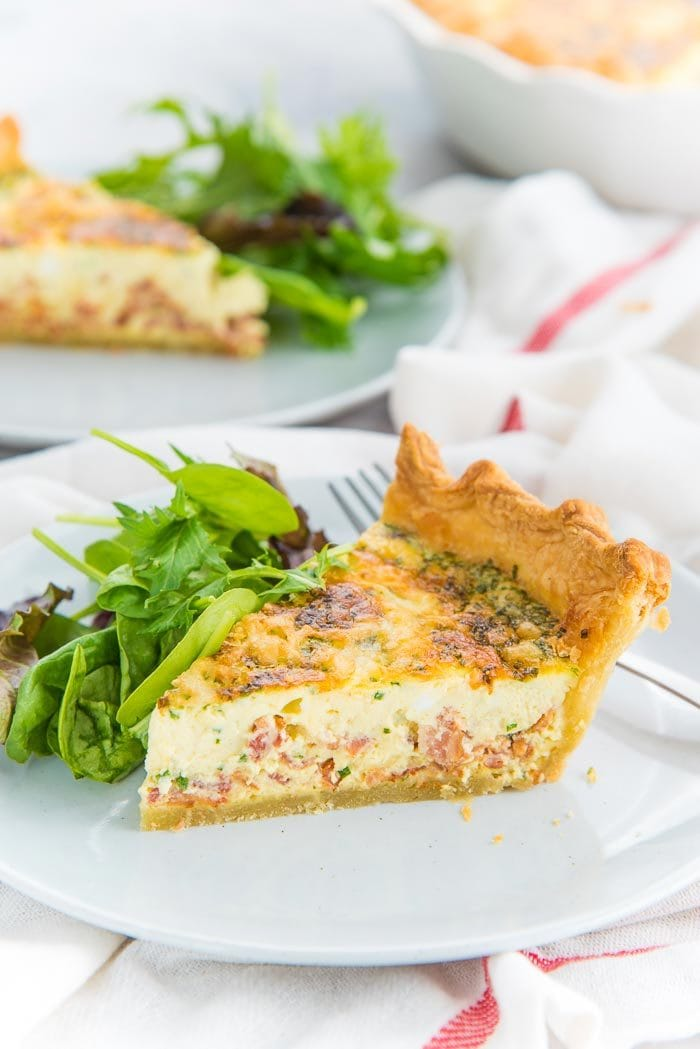 A slice of quiche lorraine on a light grey plate with a side salad
