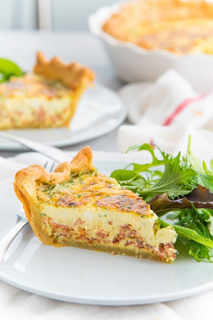 A slice of quiche lorraine, with a golden crust places on a plate with a side salad