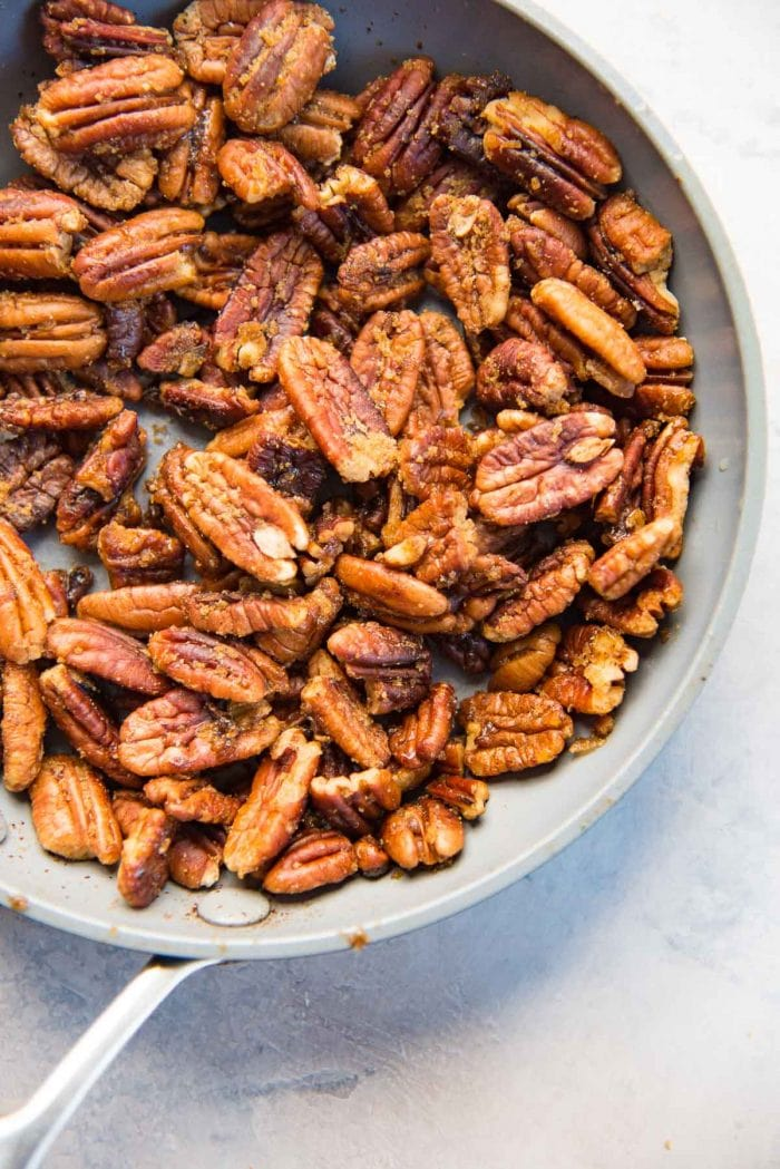Butter pecans in a non stick pan, after being coated with sugar
