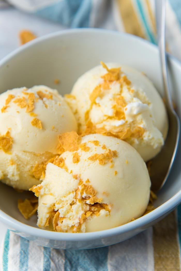 A close up of the Cereal milk ice cream scoops in a off white bowl with crushed cornflakes on top