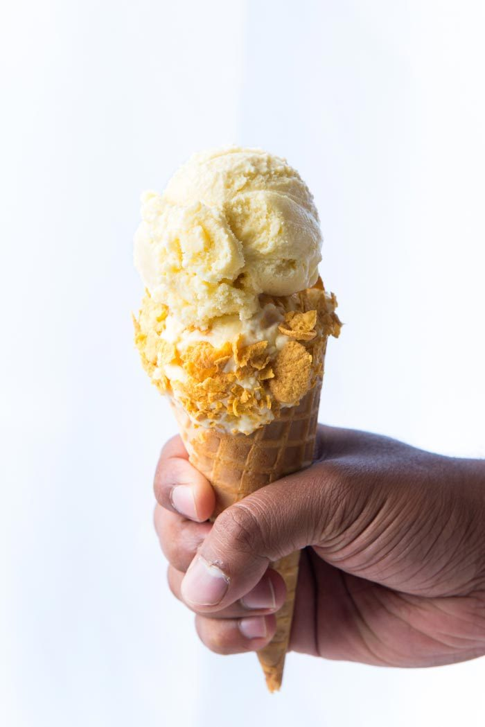 Two scoops of Cereal milk ice cream on a waffle cone, with crushed cornflakes on the bottom scoop, as a serving suggestion.