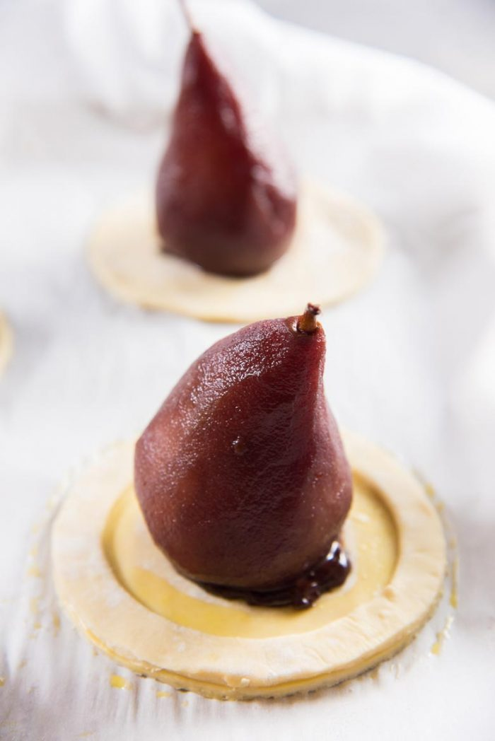 An assembled chocolate stuffed poached pear tarts