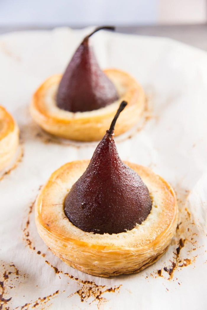 Freshly baked chocolate stuffed poached pear tart on a parchment paper
