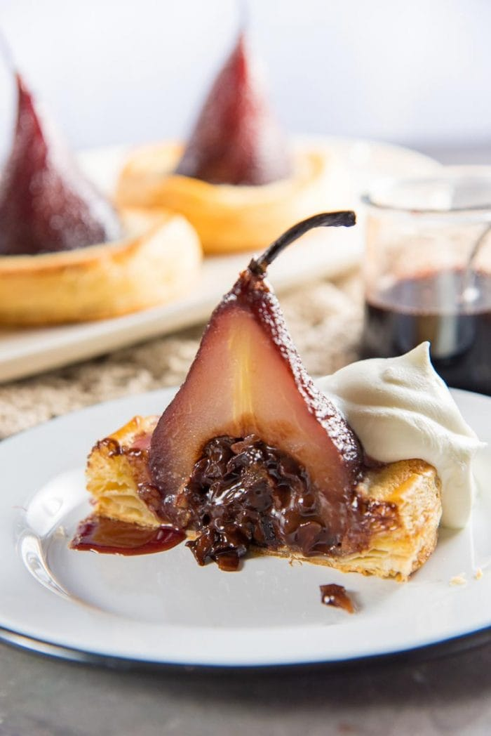 A pear tart cut in half, showing the gooey chocolate filling in the middle.