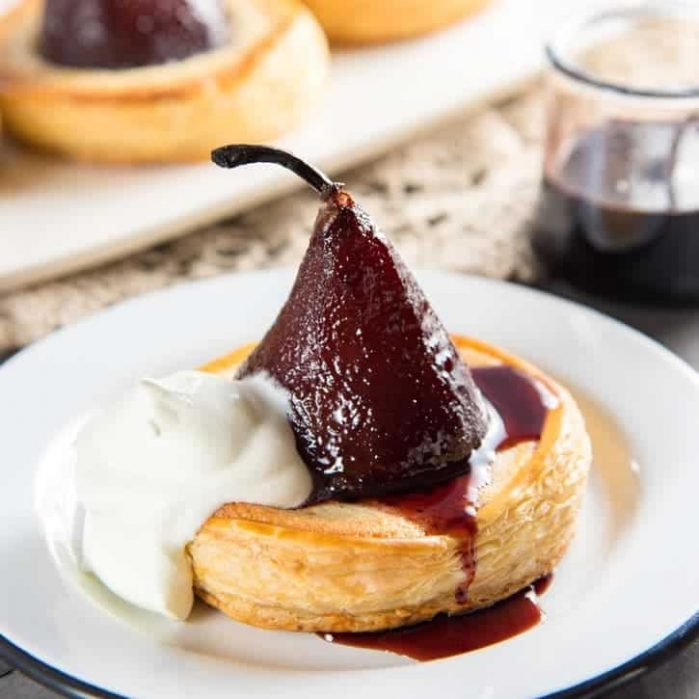 Delicious poached pear tarts, baked in frangipane and filled with a gooey chocolate filling. A show-stopping dessert!