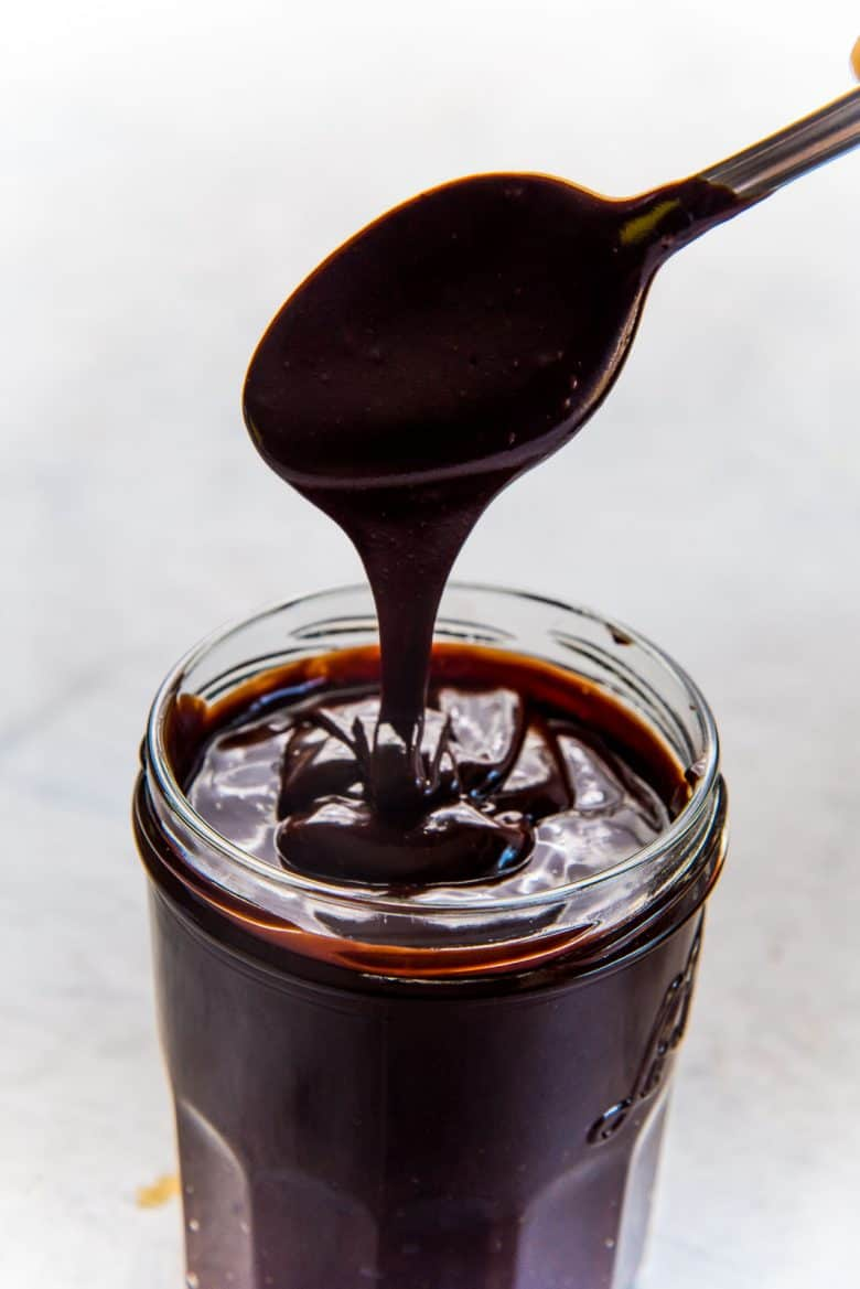 A jar full of homemade hot fudge sauce with a spoon full of hot fudge sauce showing the consistency
