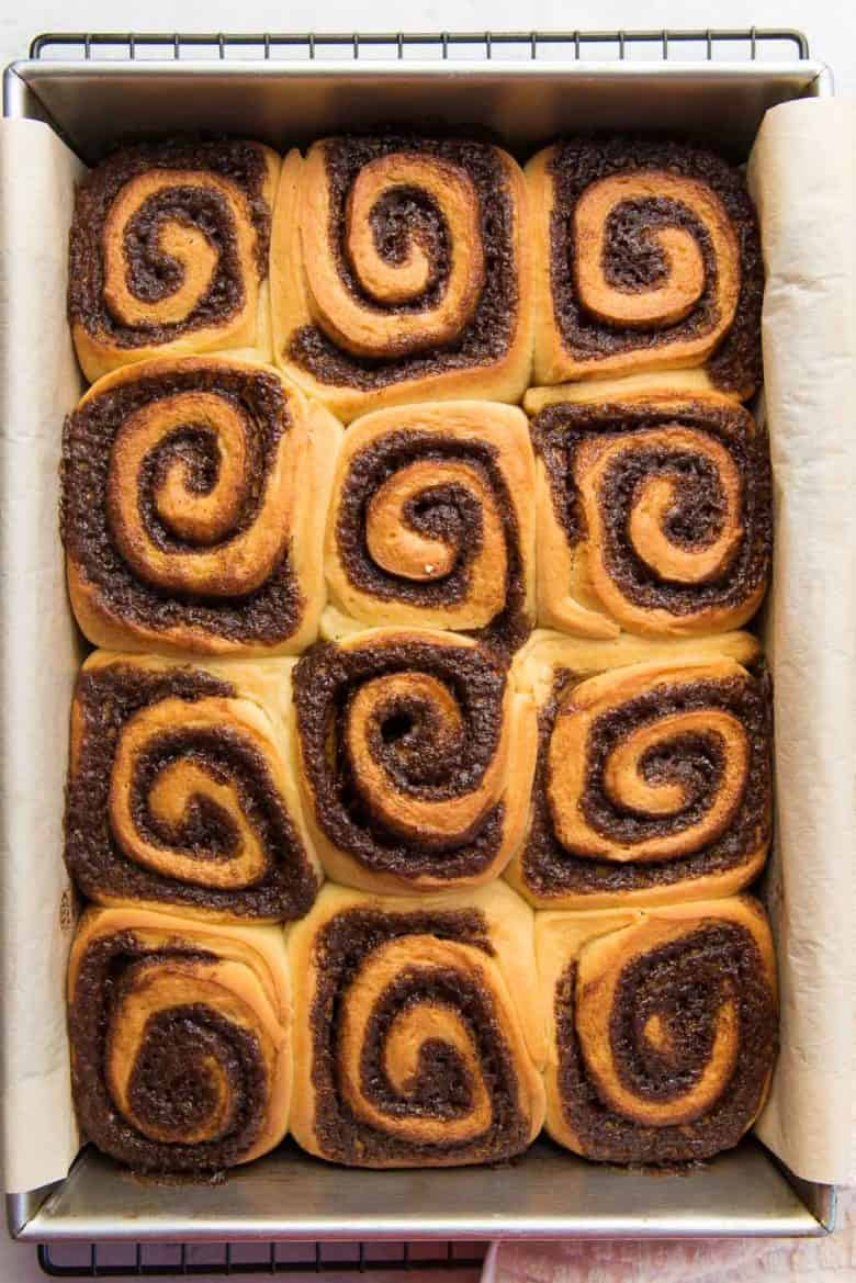 Freshly baked cinnamon rolls straight out of the oven, in a baking pan.