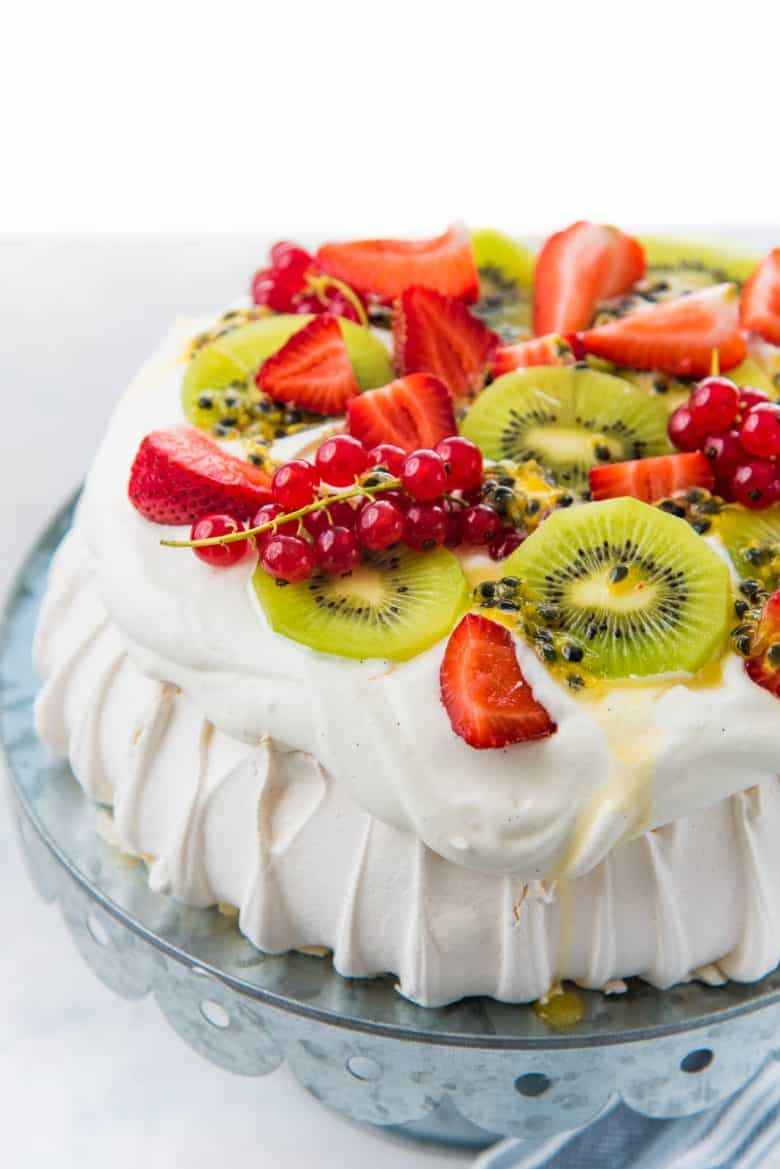 A perfect pavlova showing the whipped cream topping with fresh fruits on top
