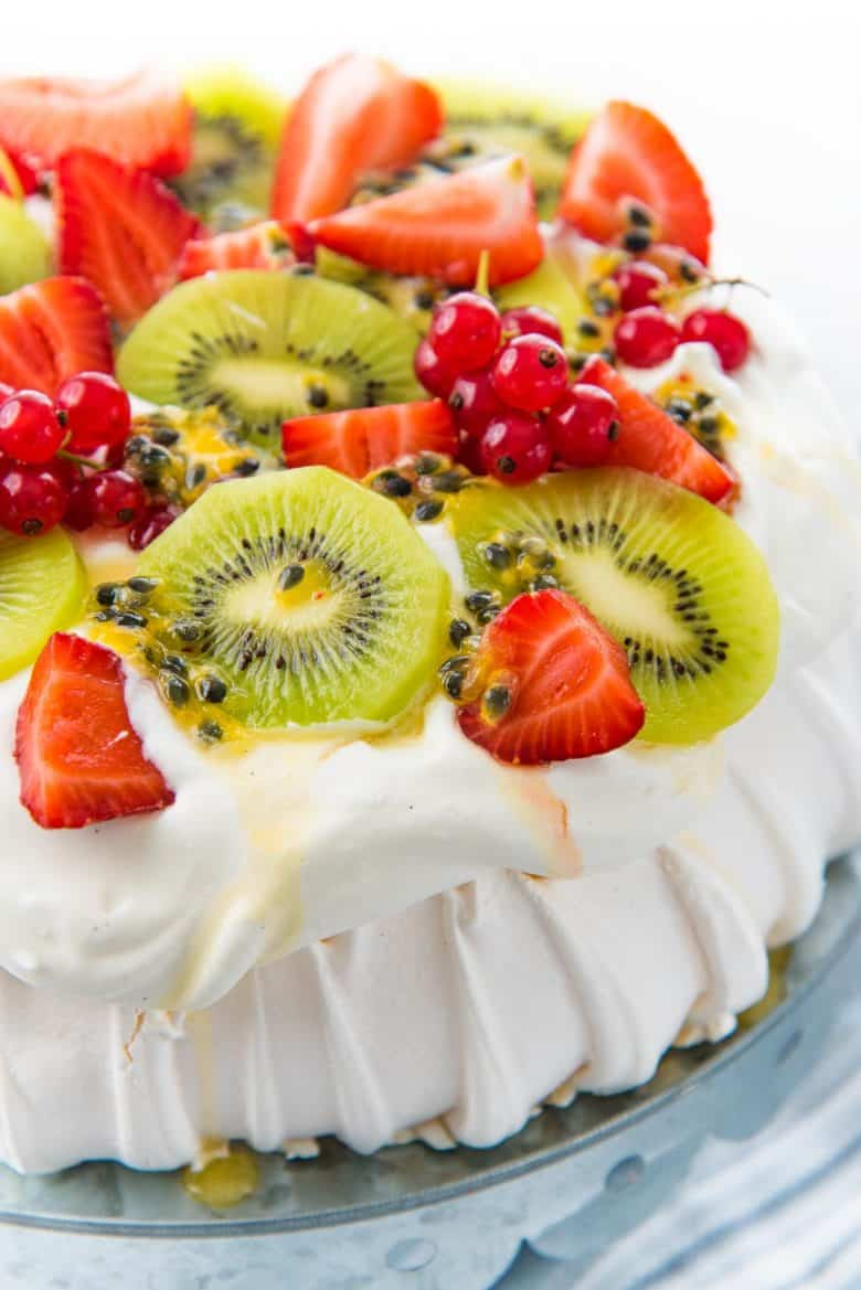 A close up of a pavlova on a cake stand, topped with whipped cream, kiwi fruit, strawberries, passion fruit and redcurrants