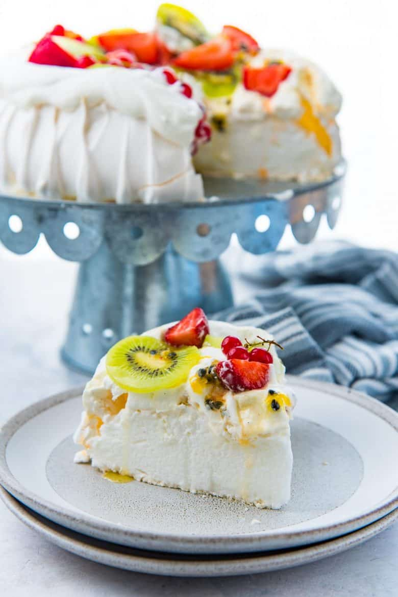 A slice of pavlova on a grey plate, topped with cream and kiwifruit, strawberries and passion fruit