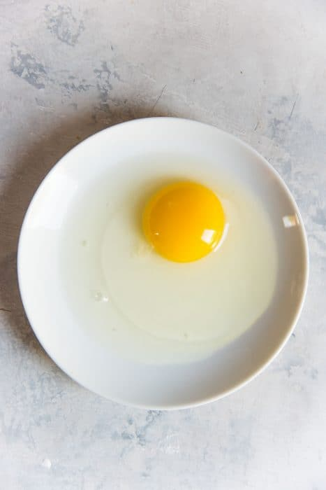 An old egg on a white plate, showing the loose and runny egg white around the yolk