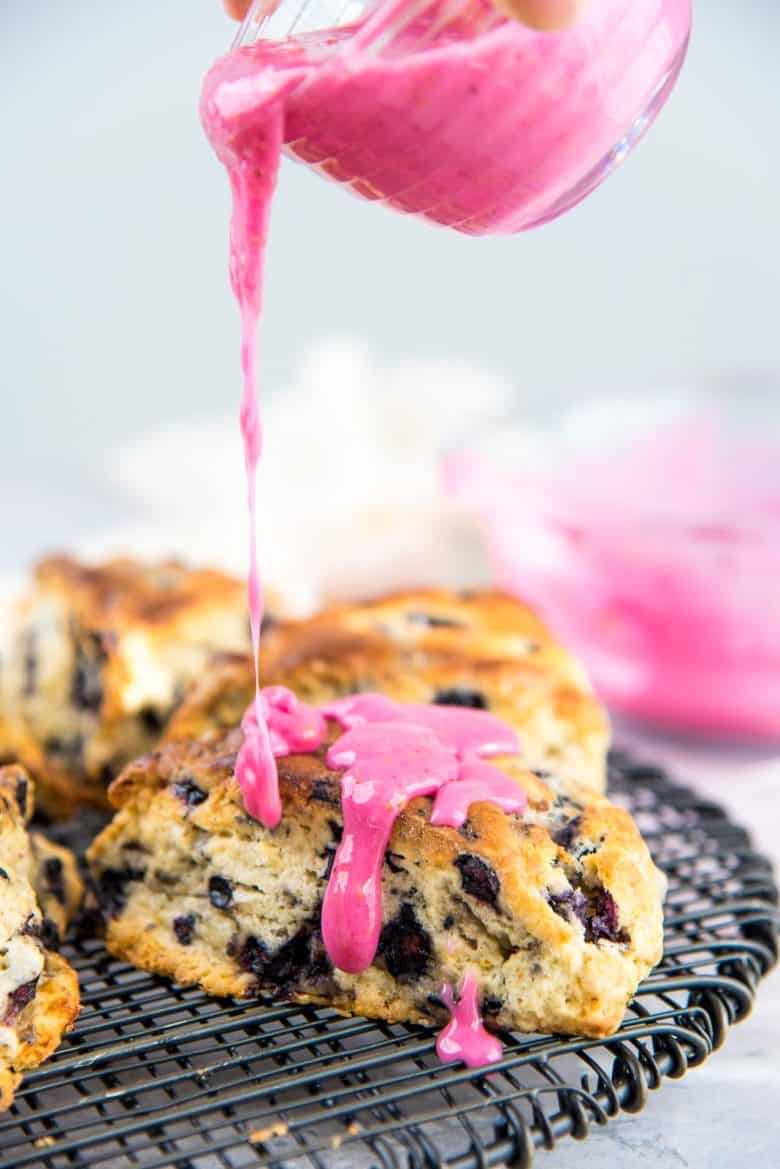 Blueberry scone on a wire rack with the blueberry lemon drizzle being poured on top.
