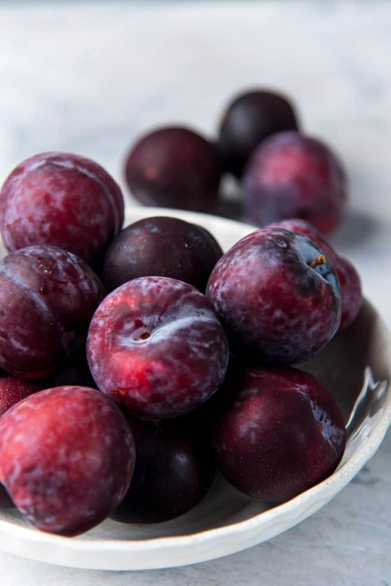 A bowl of black plums