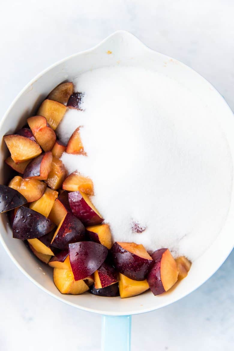 Plums cut into small pieces in a bowl with white sugar