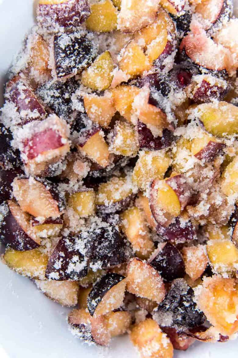 Chopped plums mixed with white sugar to macerate overnight