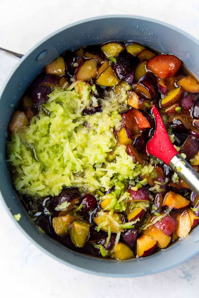 Macerated plum sugar mix in a large pot with grated green apple to make homemade plum jam