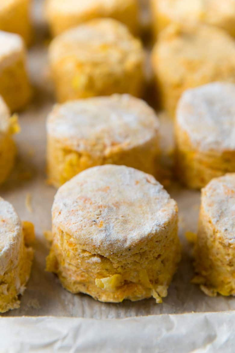 Frozen cheddar cornmeal biscuits on a lined baking tray