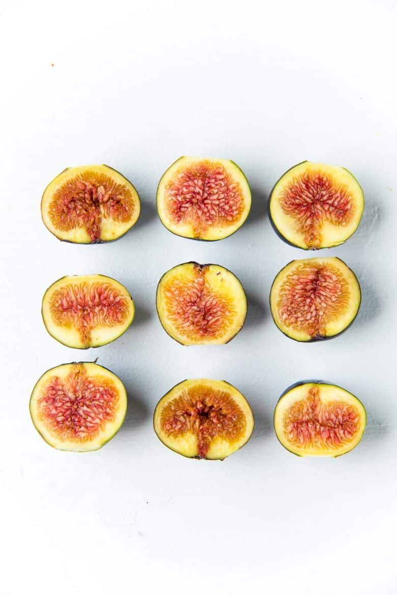 Halved fresh figs on a white background